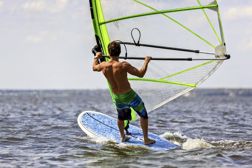 Rear view of young windsurfer